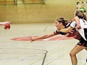 Den Ball auch unter Bedrängnis noch zur Nebenfrau zu bringen, das zeichnet gute Handballer aus. Hollenstedts Dina Bergmane-Versakova (rotes Trikot) ließ sich auch von diesem Klammergriff um den Hans von Henstedts Tina Pejic nicht beirren. Foto: rin